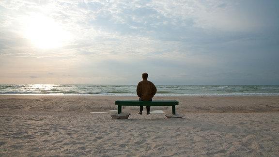 Mann sitzt auf einer Bank und schaut auf das stürmische Meer