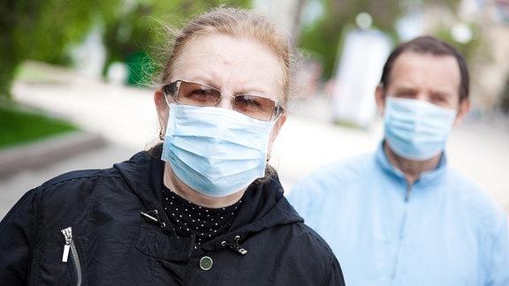 Zwei Menschen mit Mundschutz