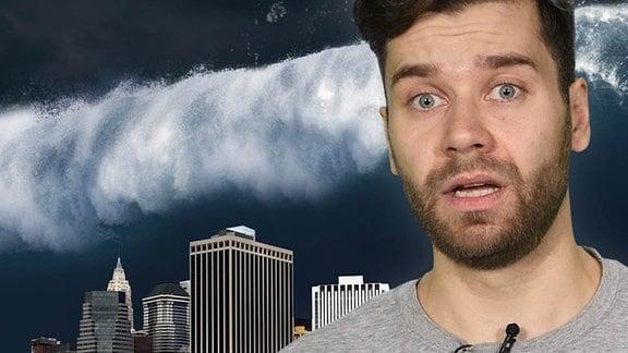 Ein Mann mit Mikrofon, dahinter Hochhäuser und eine riesige Welle.