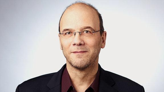Ein Mann mit Brille lächelt