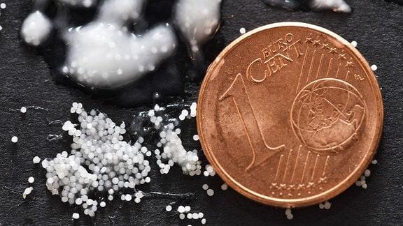 Mikroplastik-Partikel im Größenvergleich neben einer Ein-Cent-Münze