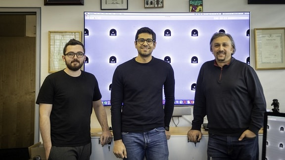 Drei Männer mit legerer Kleidung und dunklem Oberteil stehen vor einer Leinwand, auf der viele der kapselförmige Miniroboter zu sehen sind.