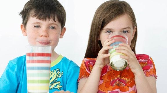 Zwei Kinder trinken ein Glas Milch