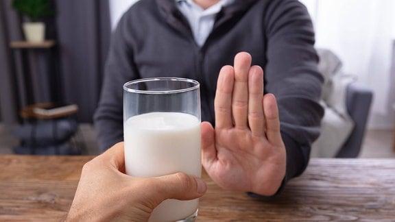 Eine Person lehnt ein Glas Milch ab