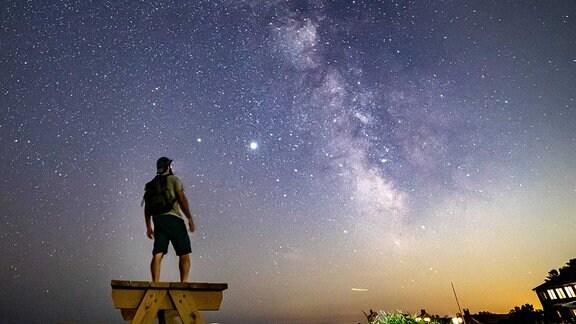 Mann steht auf einer Bank und Blickt in Sternenhimmel mit Milchstraße, Haus in der Ecke strahlt Licht aus