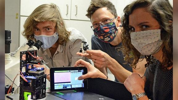 Menschen mit Mund-Nasen-Schutz-Masken posieren mit Geräten