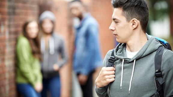 Ein Junger Mann wird von gleichaltrigen gemobbt