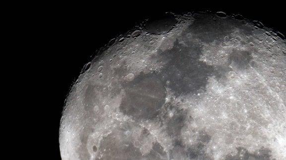 Grauer runder Himmelskörper mit Kratern, bildfüllend, Kugelschatten oben rechts