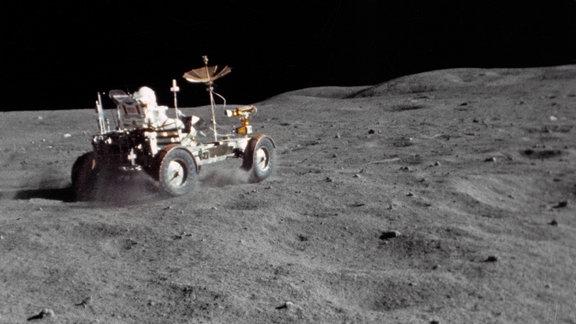 Mondauto mit Astronaut auf Mondoberfläche, fahrend