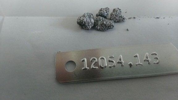 Eine Art Kieselsteine (Nahaufnahme), darunter eine Materialplakette mit der Probennummer