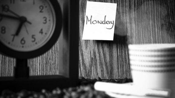 Eine Kaffeetasse und ein Post-it mit dem Wort Monday