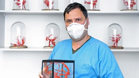 Ein Arzt mit blauem Kittel und einer Mund-Nasen-Maske hält einen Glaskubus, in dem sich ein rotes Geflecht in Form eines menschlichen Gehirns befindet. Im Regal hinter ihm stehen weitere, ähnliche rote Gebilde in Glasbehältern.