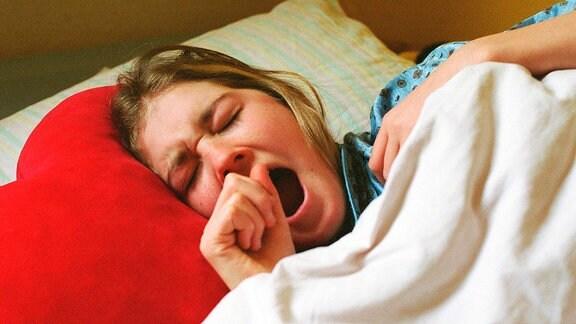 Eine Frau liegt im Bett.