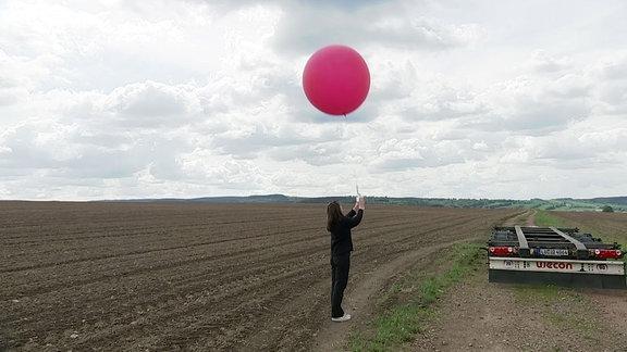 Eine Person steht neben einem Feld und hält einen Ballon an einer Schnur.