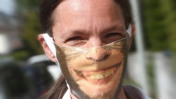 Eine Person trägt eine Mund- und Nasenschutzmaske mit Aufdruck eines lachenden Schimpansen.