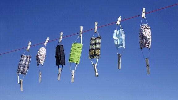 Auf einer Leine hängen sieben verschiedene Mundschutze.