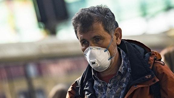 Ein Mann mit weißem FFP-Mundschutz
