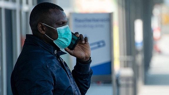 Ein Mann mit grünem, dünnen OP-Mundschutz telefoniert