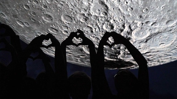 Hände formen Herzen - vor dem Mond.