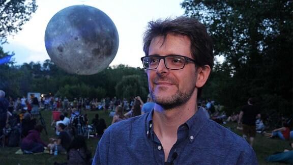 Ein Mann - hinter ihm der Mond
