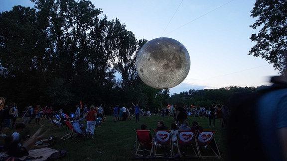 Der Mond hängt zwischen den Bäumen.