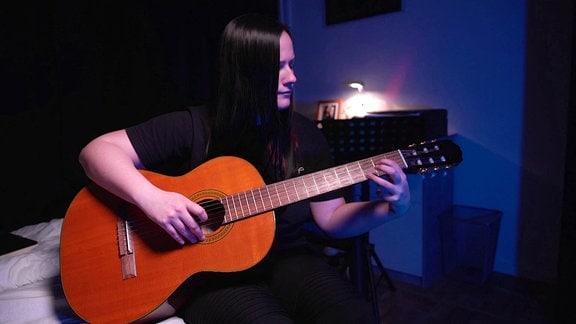 Eine Frau spielt Gitarre.