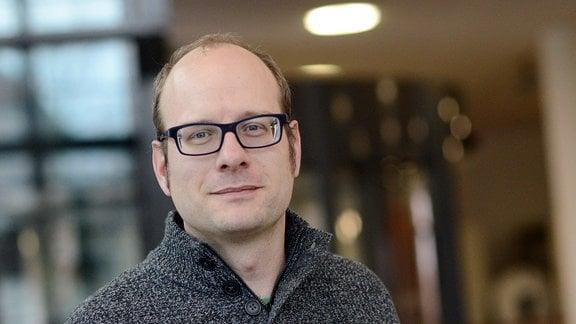 Der Forscher Andreas Musolff vom Helmhotz-Zentrum für Umweltforschung Leipzig trägt einen grauen Wolpullover, hat eine schwarze Hornbrille, eine Halbglatze und blonde Haare.
