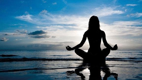 Model im Gegenlicht macht Yoga im Wasser