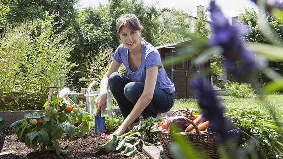 Junge Frau bei der Gartenarbeit.