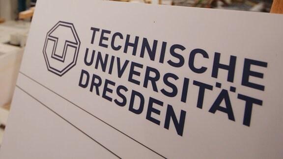 Ein Schild mit Technische Universität Dresden in der Fakultät Bauingenieurwesen / Professur für Wasserbau.
