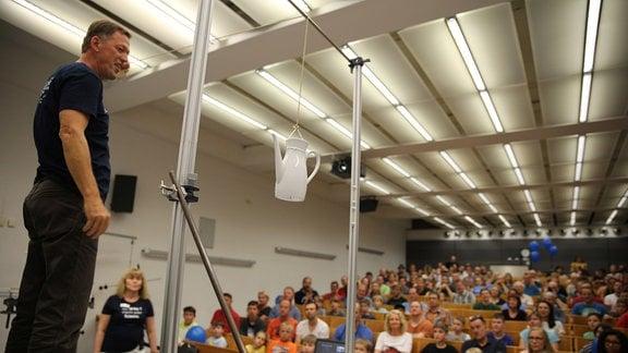 Ein Mann steht auf der Bühne, der Hörsaal vor ihm ist voller Menschen. Er zeigt ein Experiment, bei dem weine weiße Porzelankanne an einem Rechteckigen Rahmen aufgehängt ist.