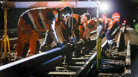 Gleisbauer verlegen nach Betriebsschluss Gleise einer U-Bahn.