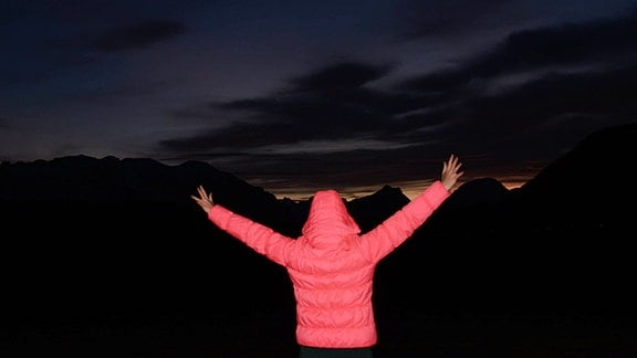 Eine Person steht vor einem Nachthimmel.