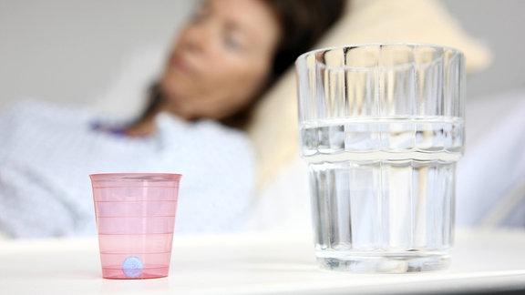 Eine Patientin in einem Krankenbett, neben ihr ein Nachttisch mit einem Wasserglas und einem Medikamentenbecher