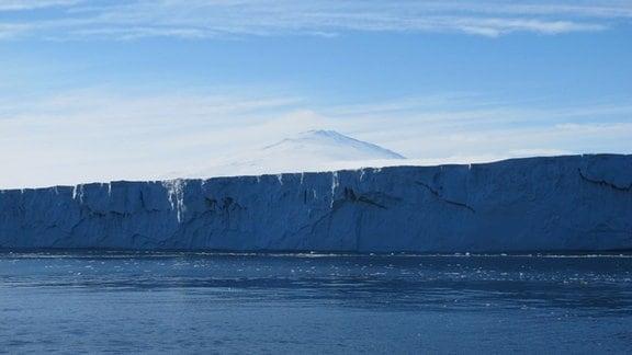 Die Abbruchkante des Nansen Eisschilds in der Antarktis. Im Hintergrund ist der schneebedeckte Berg Mount Melbourne zu sehen.