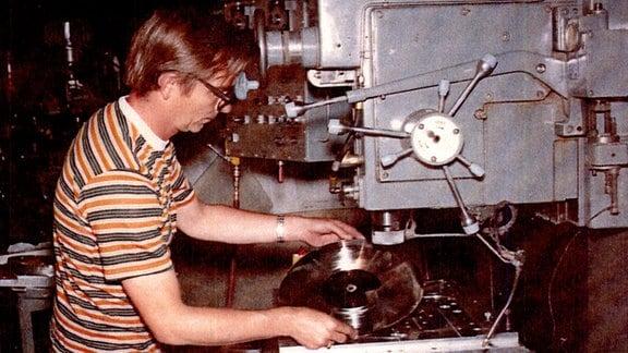 Mann arbeitet an Produktionsmaschine