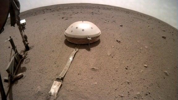 Seismometer der Marssonde InSight auf der Marsoberfläche an der Landestelle. Vom Standpunkt der Kamera führt ein Kabel über den Boden zu einer kleinen weißen Kuppel, bei der es sich um das Seismometer handelt.