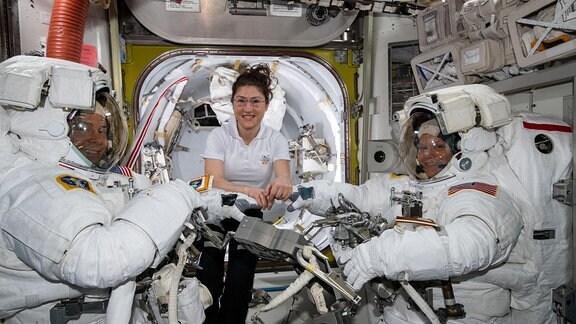 Nick Hague (mit Raumanzug), Anne McClain (mit Raumanzug) und Christina Koch in der ISS vor ihrem Weltraumspaziergang, in der ISS schwebend