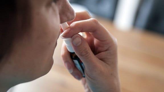 Eine Frau hält in ihrer Hand ein Nasenspray, welches sie bei Schnupfen in ihrer verstopften Nase anwendet, um die Nasenschleimhaut abzuschwellen.
