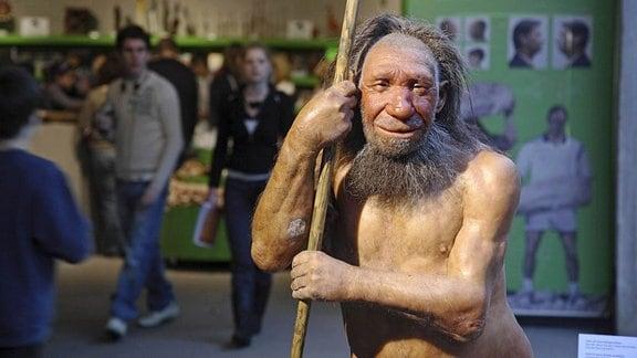 Figur eines Neandertalers und Besucher im Neandertalmuseum Mettmann