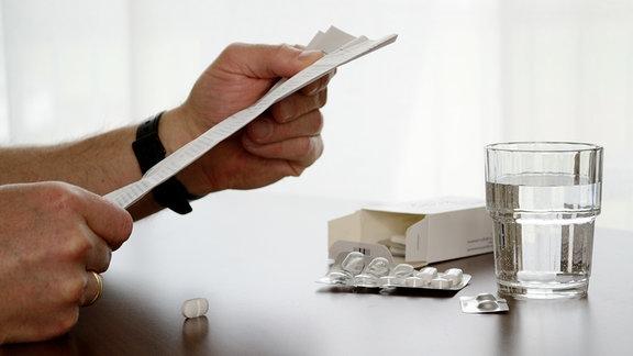 Person liest Packungsbeilage, am Tisch sind Tabletten und Glas Wasser