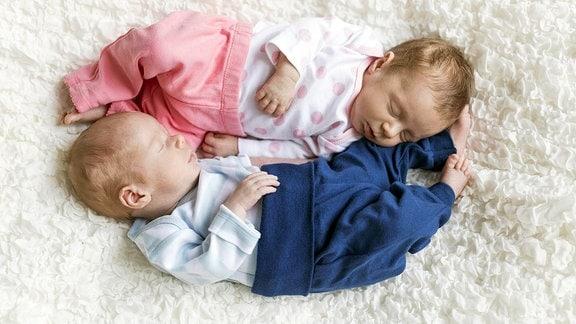 Zwei Zwillingsbabys liegen schlafend auf einer Kuscheldecke.
