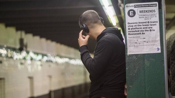 Mann mit Kopfhörern in einer U-Bahn-Station mit dem Rücken zum Betrachter, drückt auf einen Knopf am Kopfhörer