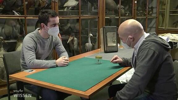 Spinnenforscher Robert Klesser und Enrico Runge an einem Tisch mit der Nosferatu-Spinne