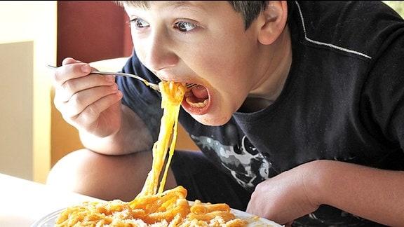 Ein Junge isst Nudeln