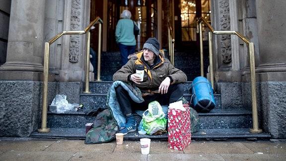 Ein obdachloser Mann sitzt in Manchester auf den Stufen des Britannia Hotels.
