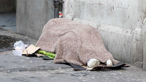 Ein Obdachloser liegt zugedeckt auf einem Fußweg.