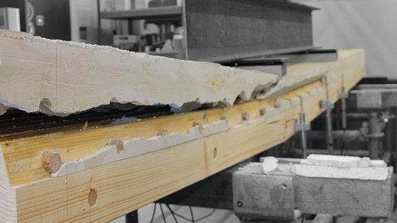 Ein massiver Holzbalken, der auf der Oberseite mit einer dicken, festen, weißen Schicht bedeckt ist.