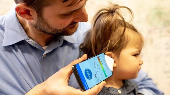 Ein Mann hält einem Kind ein Smartphone ans Ohr