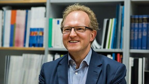 Lächelnder Mann vor einer Bücherwand